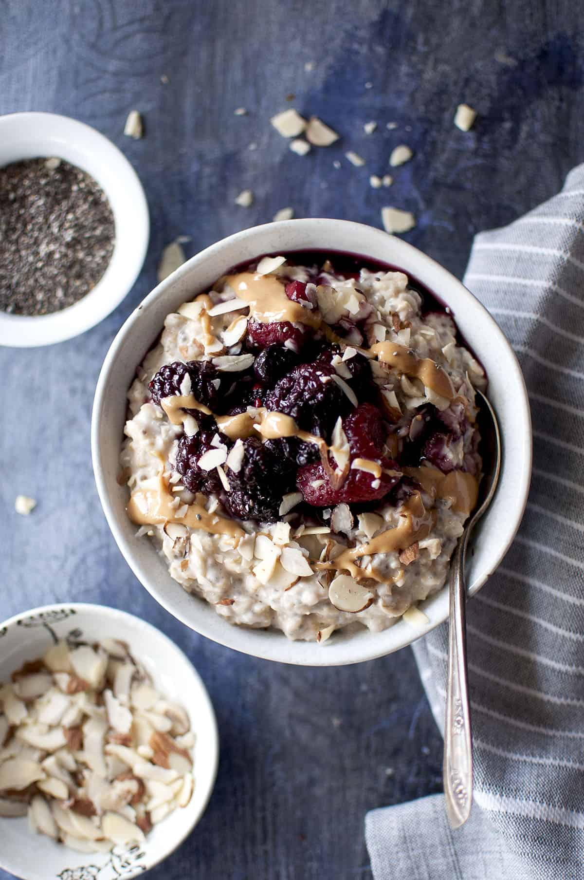 Grey bowl with oat and chia porridge topped with chopped nuts, berries and peanut butter
