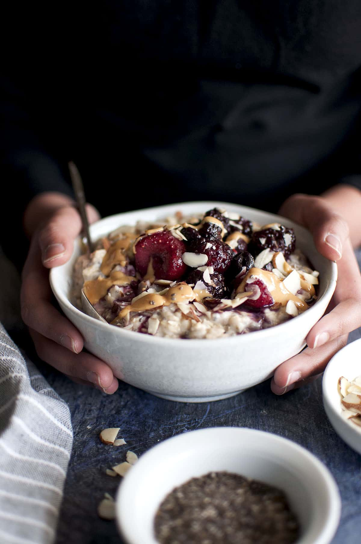 Hand holding a bowl of oatmeal porridge topped with berries
