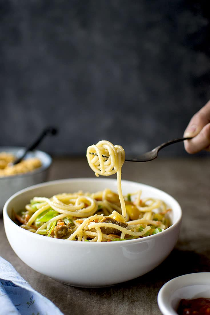 White bowl with noodles and a fork lifting the noodles
