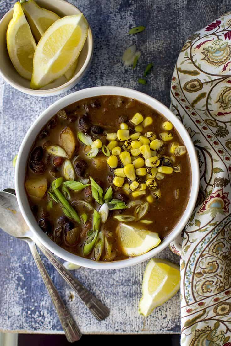 Bowl of Black bean veggie soup with lemon wedges