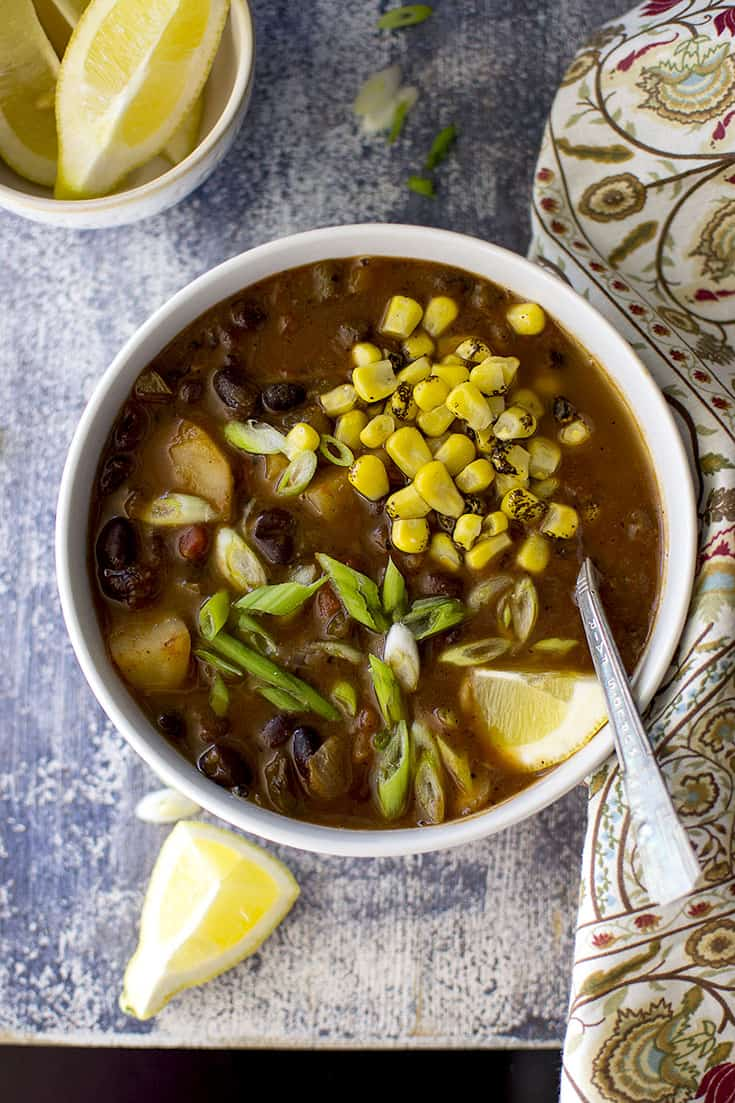 Bowl of Black bean veggie soup with roasted corn and lemon wedges