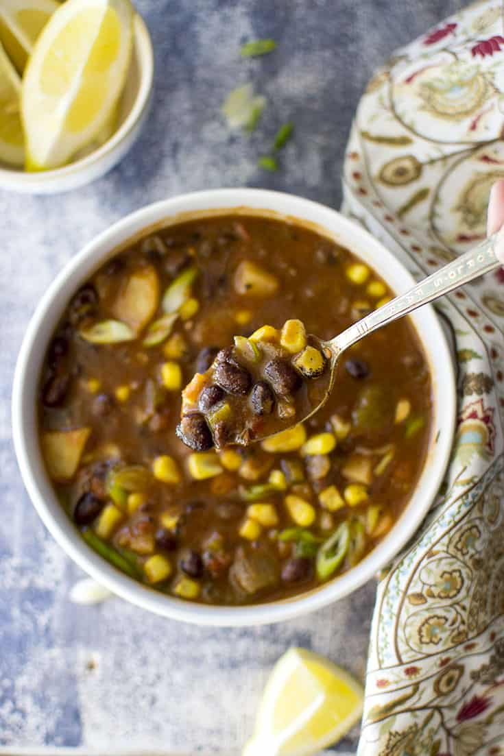 Spoon and bowl with black bean soup with vegetables