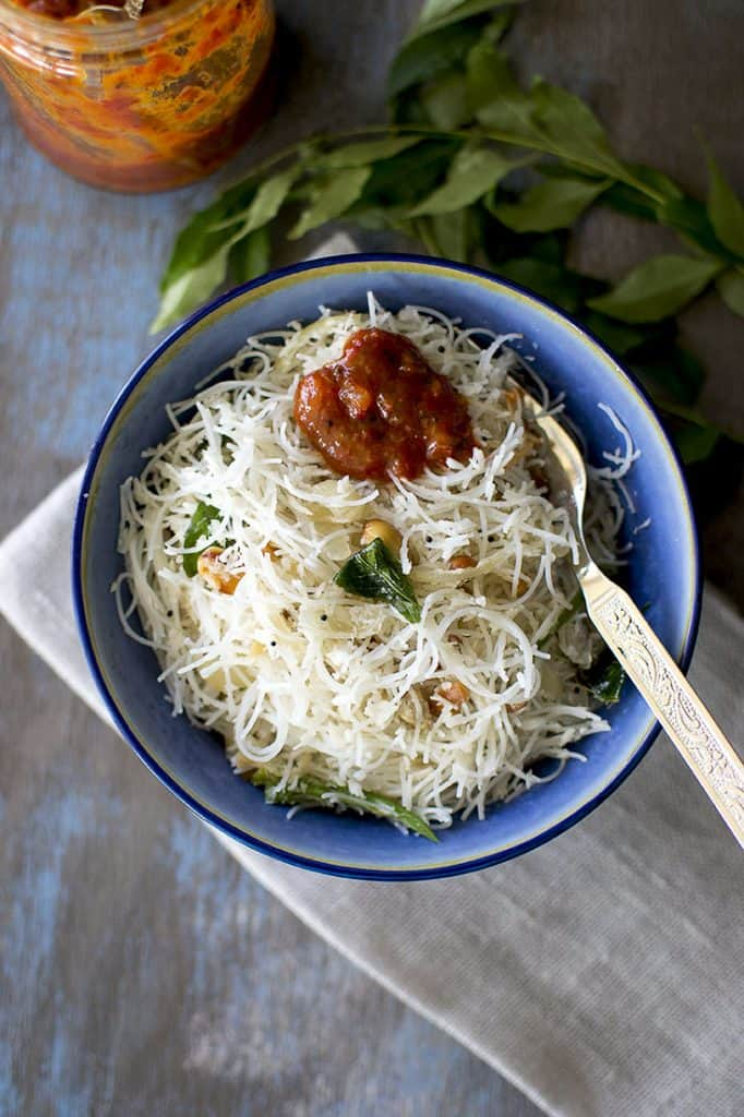 Bowl of rice noodles with pickle on top.