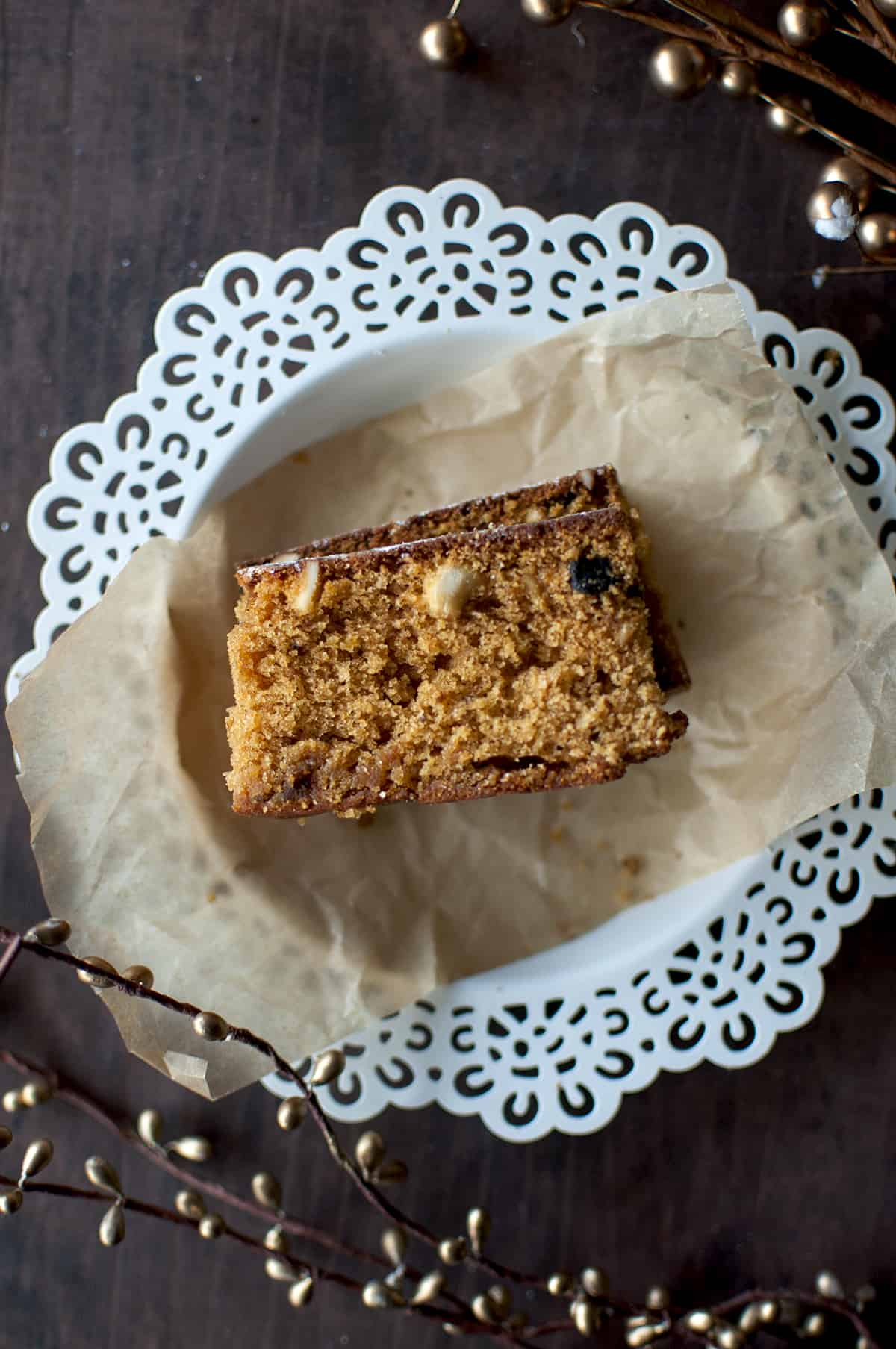 White plate with a parchment and a slice of fruit cake