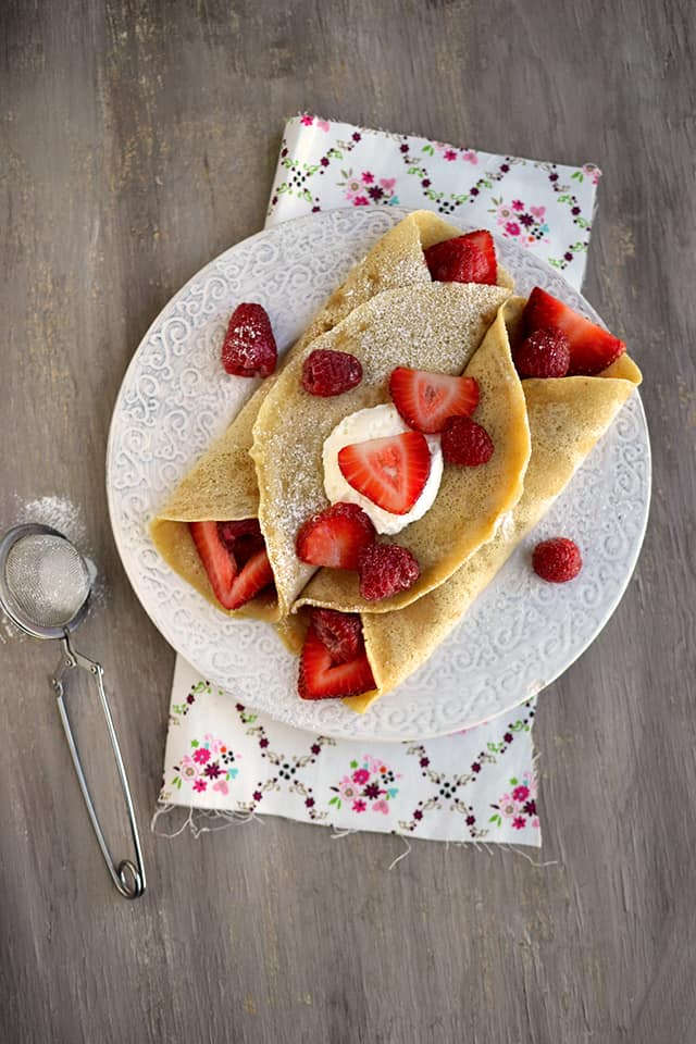White plate with crepes stuffed with berries and topped with whipped cream