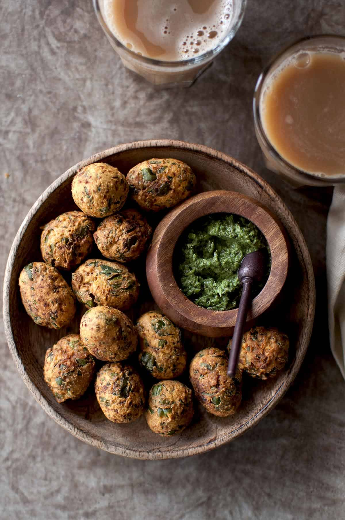 wooden bowl with fried methi muthiya and a bowl of green chutney