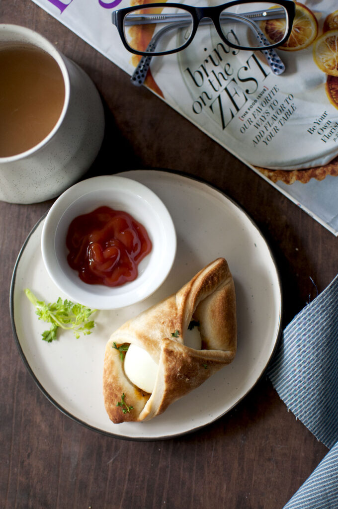 Black plate with egg puff and small bowl with ketchup and a mug of tea