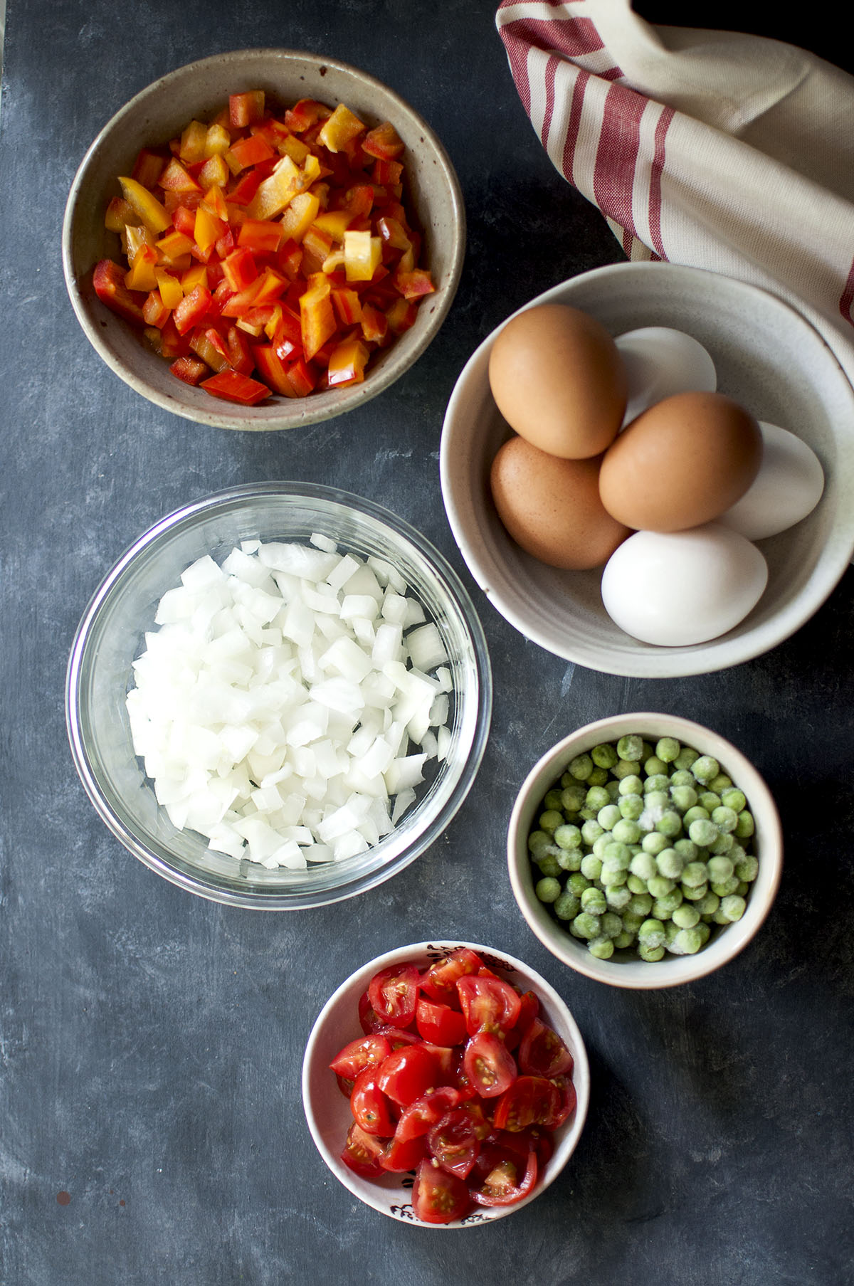 Bowls with chopped bell peppers, onions, tomatoes, frozen peas and bowl of white & brown eggs