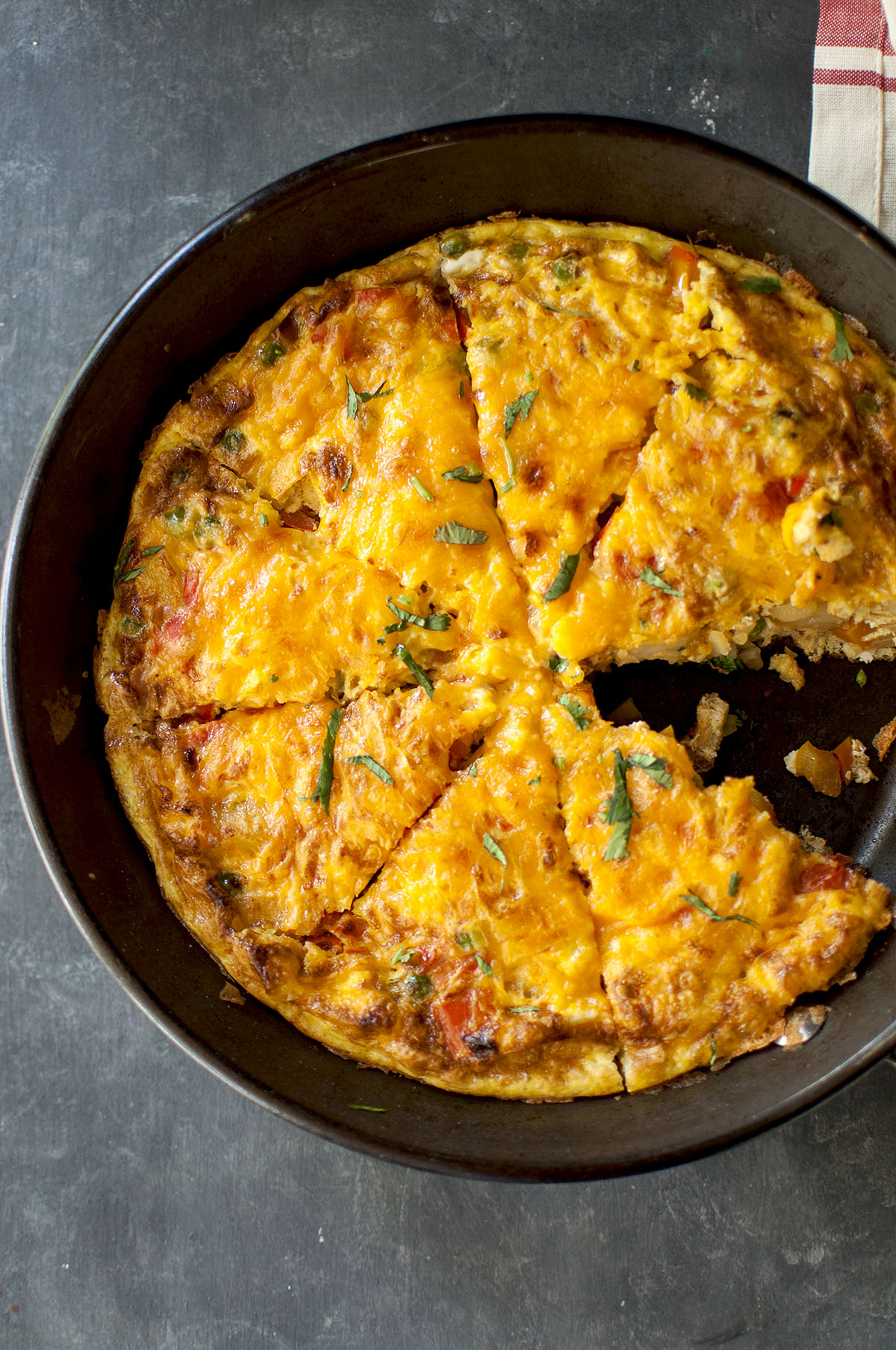 Nonstick skillet with cheesy frittata with a wedge taken out