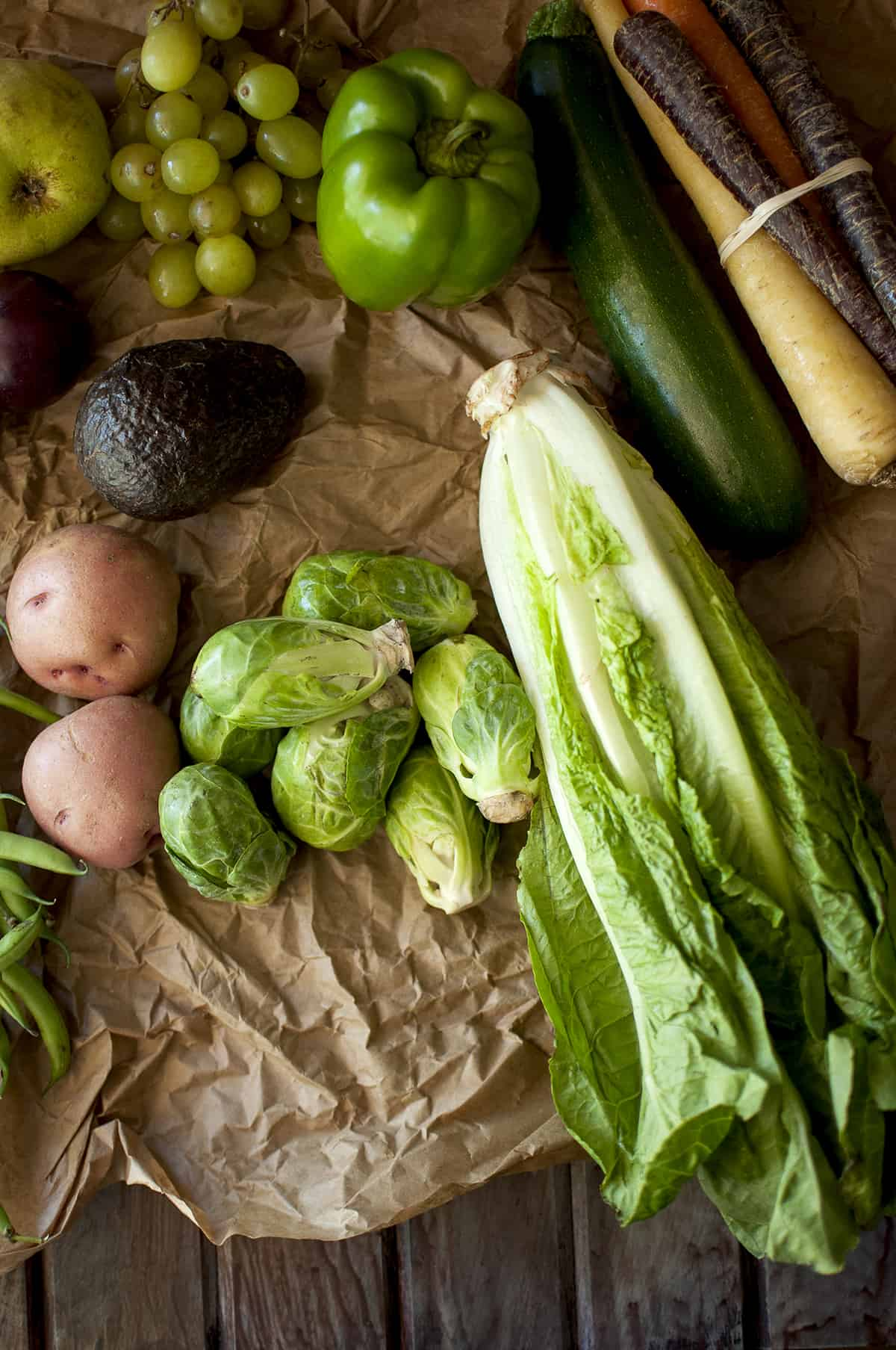 Brown paper with lettuce, brussel sprouts, potatoes, avocado, pepper, zucchini, carrot, grapes and pear