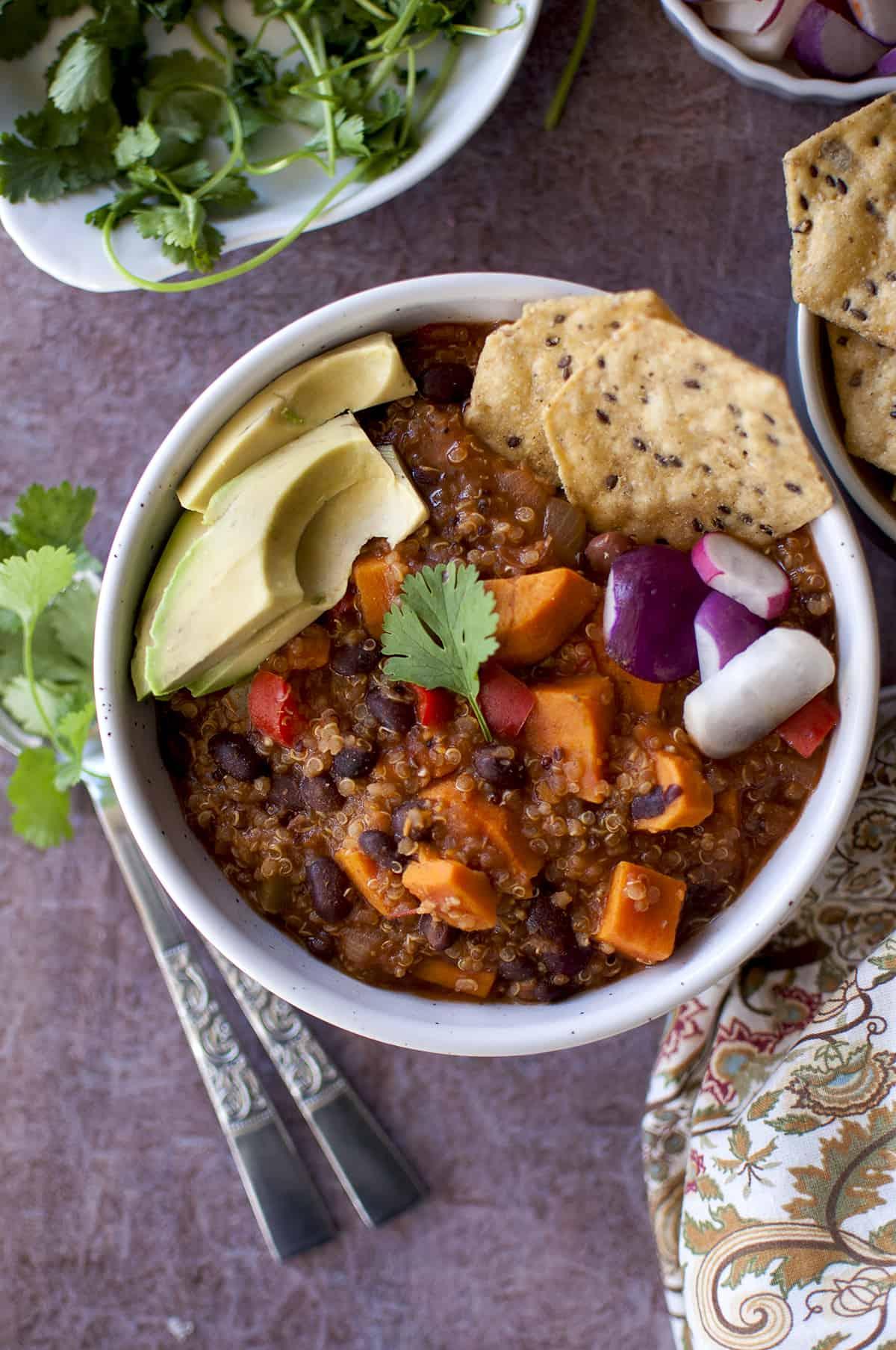 White bowl with the sweet potato quinoa chili topped with avocado, radish, cilantro and chips