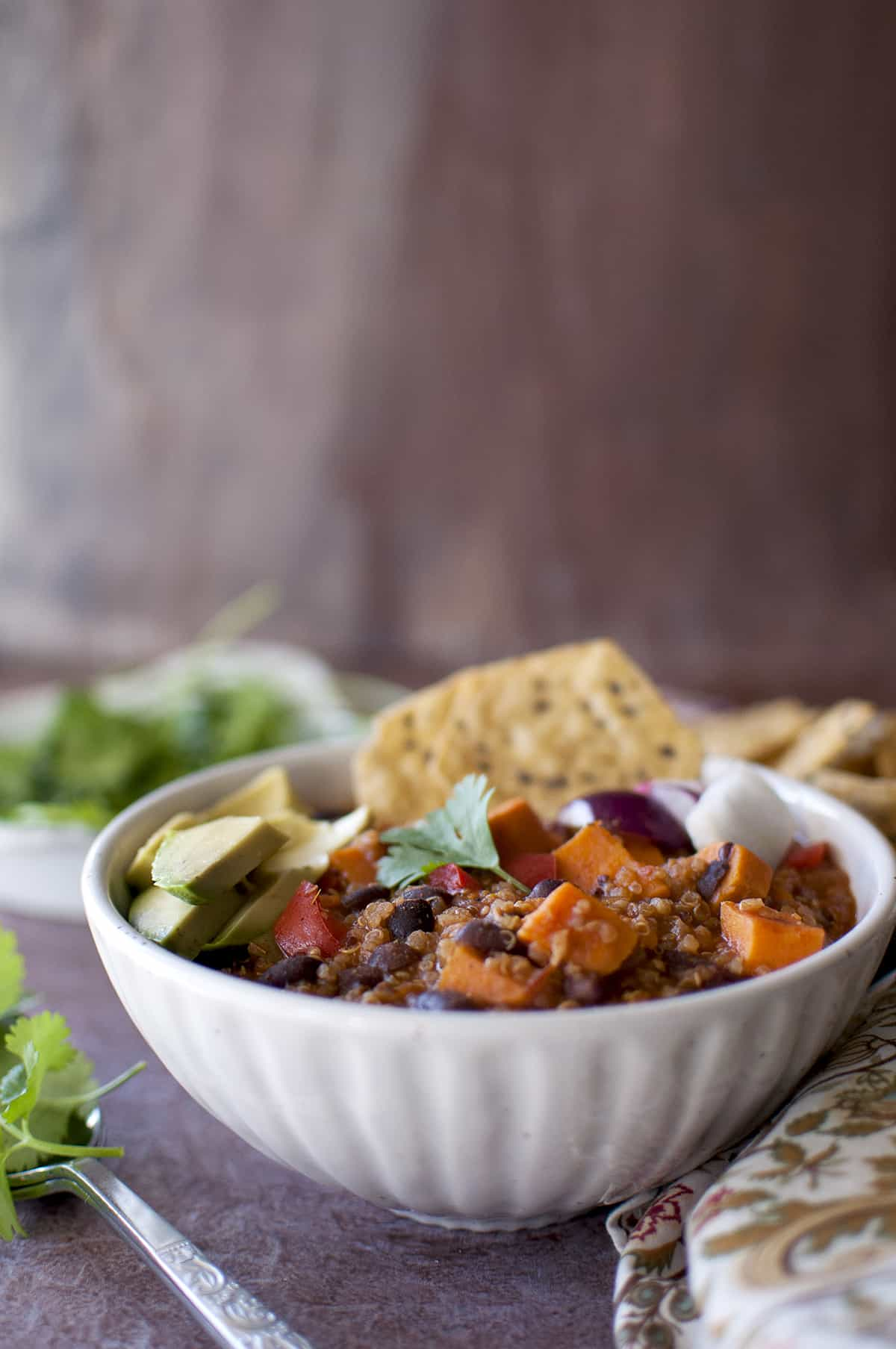 White bowl with quinoa chili with toppings