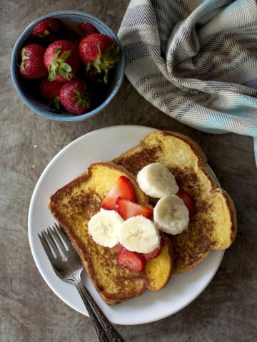 White plate with 2 slices of eggless French toast topped with chopped fruit